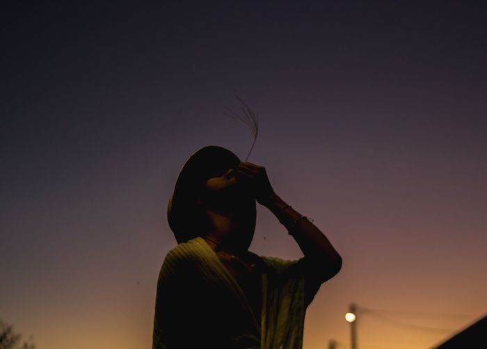Low angle view of silhouette woman standing against clear sky