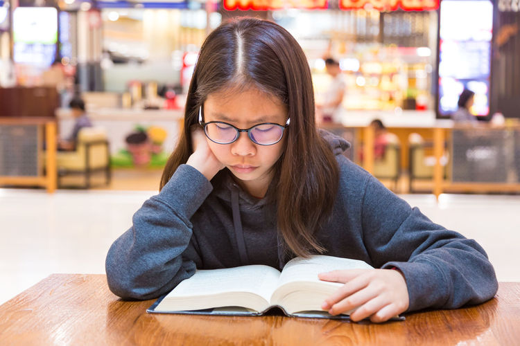 Asian teenager girl reading her book at a public place Asian  Females Reading, PA. Woman Book Childhood Concentrate Education Eyeglasses  Headshot Learning Leisure Activity Lifestyles One Person Portrait Real People Sitting Study Table Teenager,