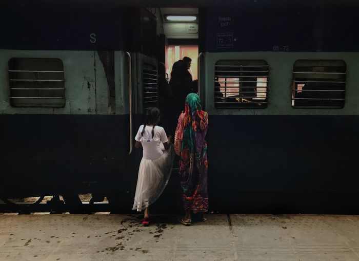 Rear view of woman standing in train