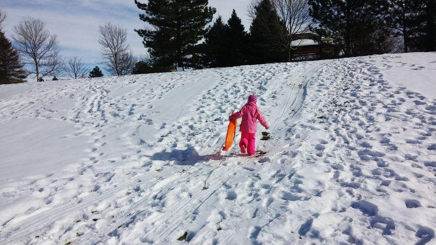Rear View Of Girl Walking On Ski Slope