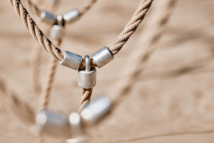 Abstract picture shot on a playground at a climbing fram with a detail with bright beige ropes connected via metal. Seen in Nuremberg, Germany, April 2019 Metal Rope Strength Connection No People Focus On Foreground Day Close-up Selective Focus Outdoors Chain Tied Up Nature Sunlight Security Hanging High Angle View Protection Sand Mode Of Transportation Outdoor Play Equipment Playground Abstract Pattern Textured  Texture Backgroud Calmness Tranquility Sunny Beautiful Bright Beige Colors Brown Men Iron Rope Ropes Connected Connectivity Teambuilding Strong Adventure Shaky Venture Bokeh Europe Germany Nuremberg Nürnberg Safety Skills  Diminishing Perspective