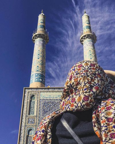 Low angle view of woman and mosque against blue sky