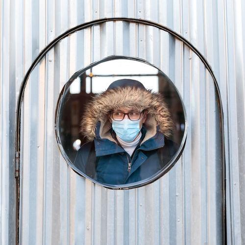 Man wearing mask looking through window