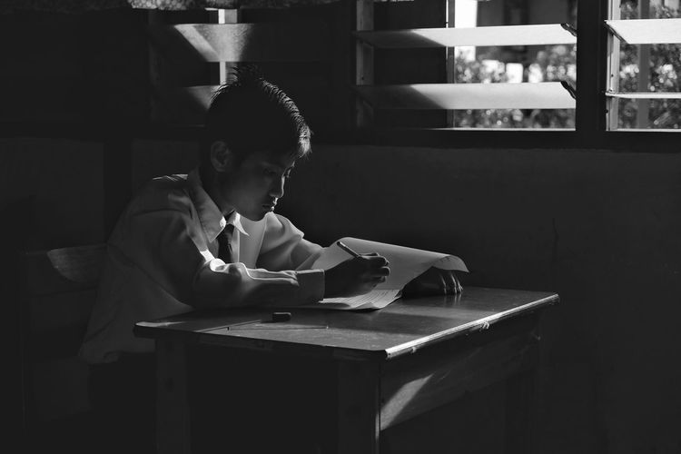 Boy writing while sitting in classroom