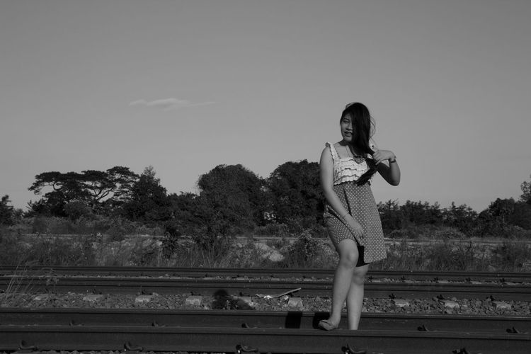 Full length of woman standing on railroad track against sky