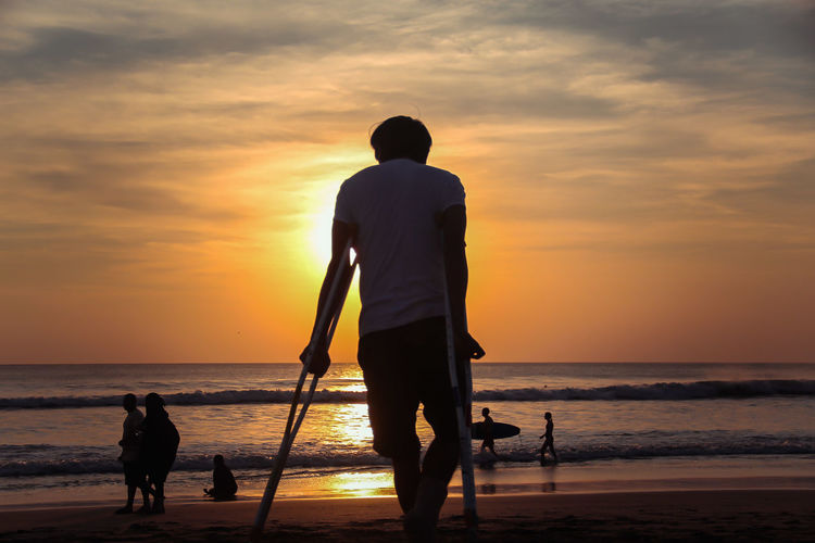 Silhouette man standing with crutches on beach against sky during sunset