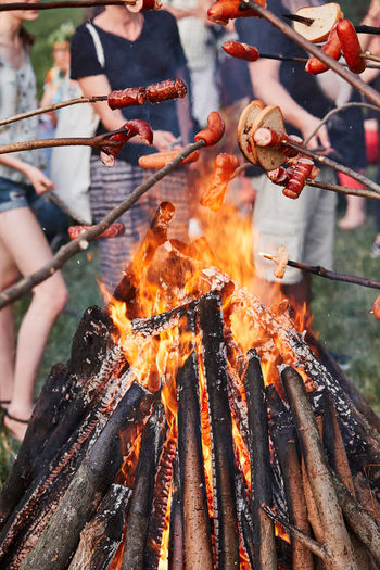 Close-up of people grilling food on bonfire