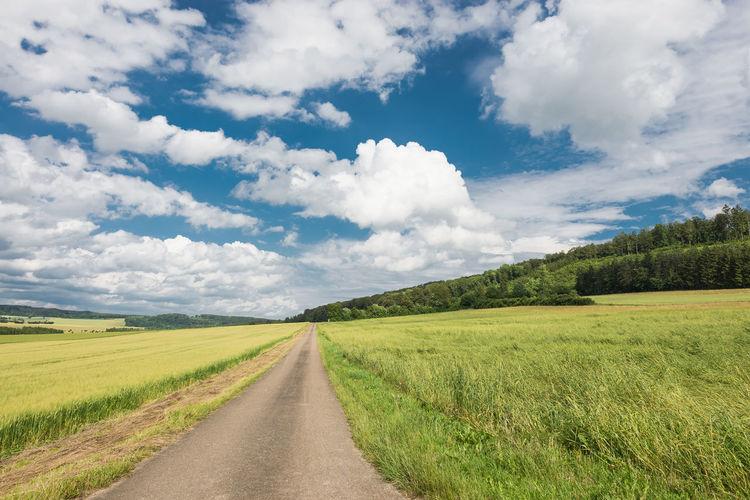 Street amidst grassy field against cloudy sky