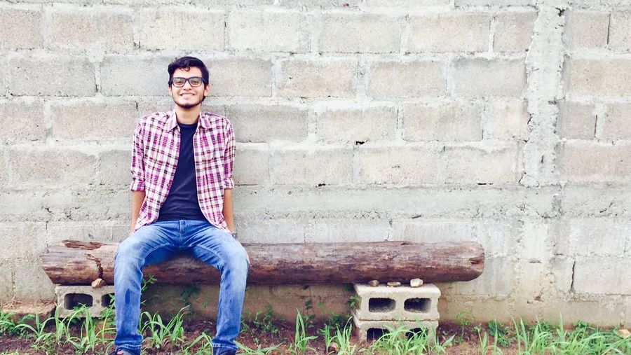 Portrait of smiling young man sitting on brick wall