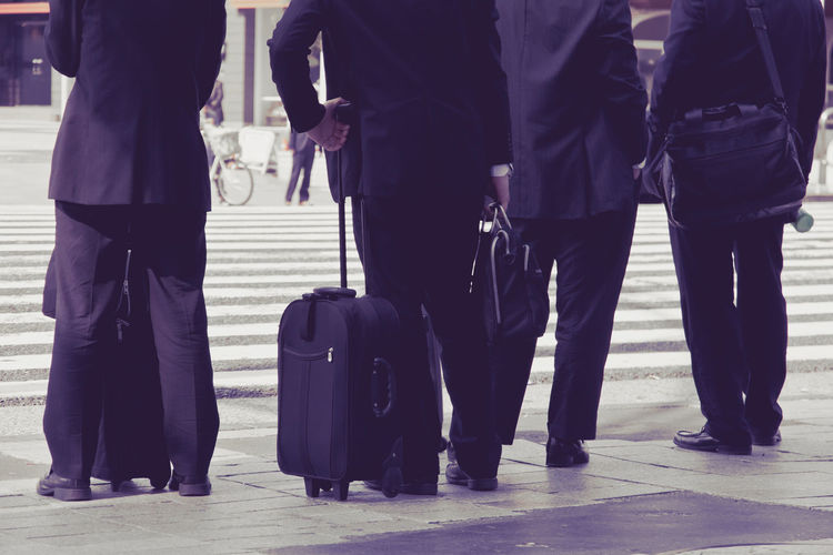 Low section of business people with luggage on road