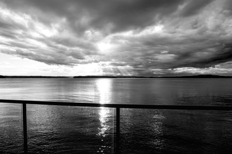 Puget sound viewed from a luxury home back yard with glass railing in black and white. Beach House Dramatic Sky Rays Of Light Travel View Beauty In Nature Black And White Cloud - Sky Cruise Day Glass Railing Horizon Over Water Lifestyles Luxury Nature No People Outdoors Sailing Scenics Sea Sky Tranquil Scene Tranquility Water Waterfront