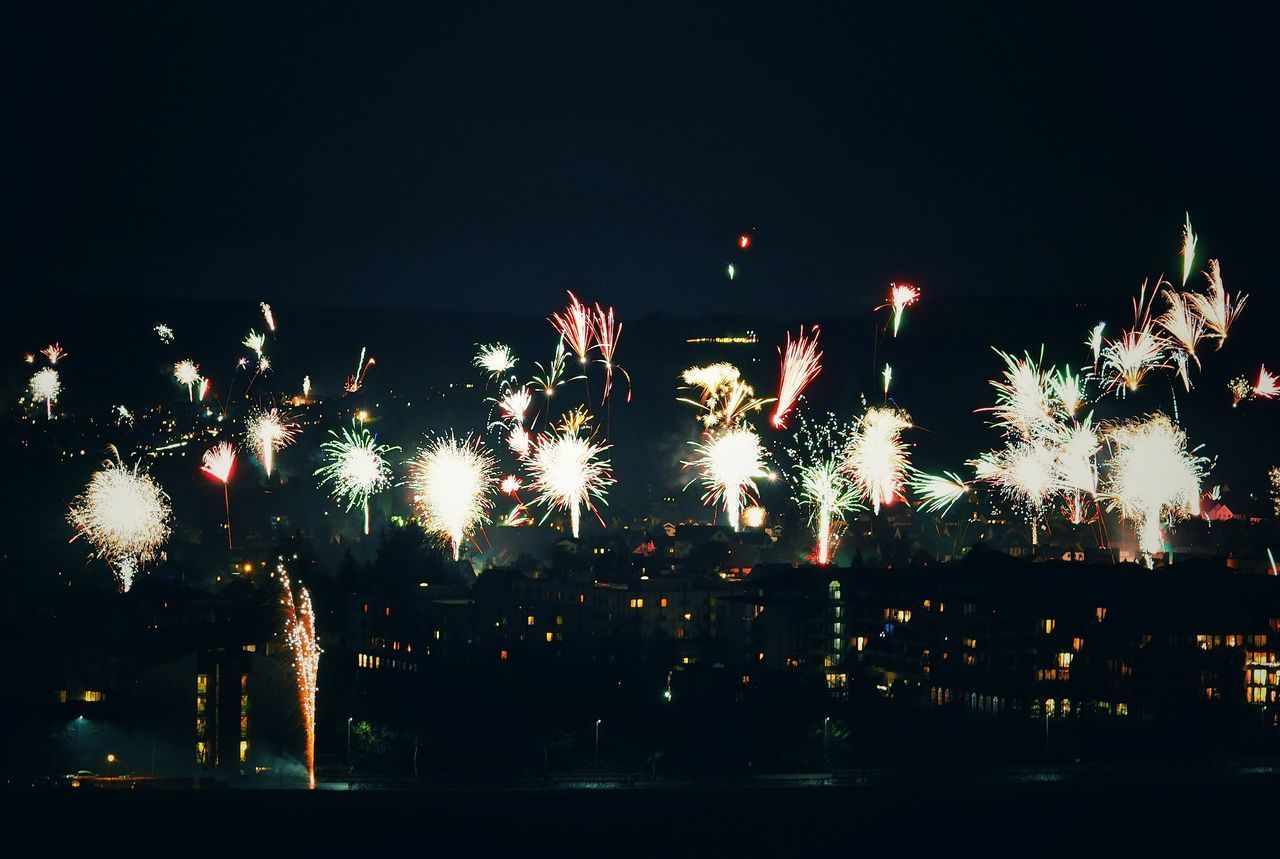 LOW ANGLE VIEW OF ILLUMINATED FIREWORK DISPLAY AT NIGHT