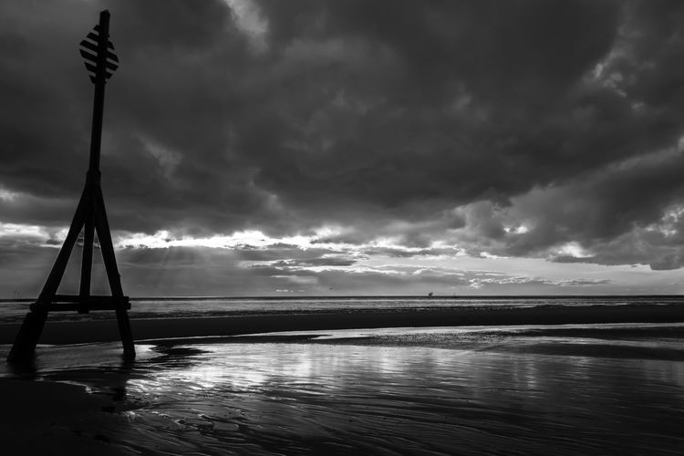 Silhouette Pole At Beach Against Cloudy Sky