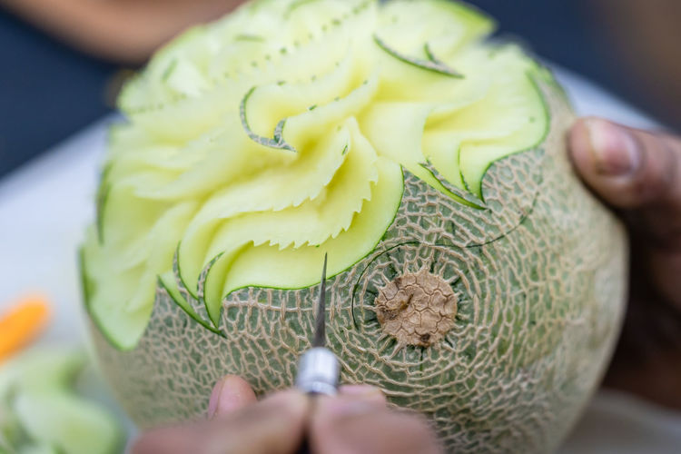Cropped hands carving cantaloupe