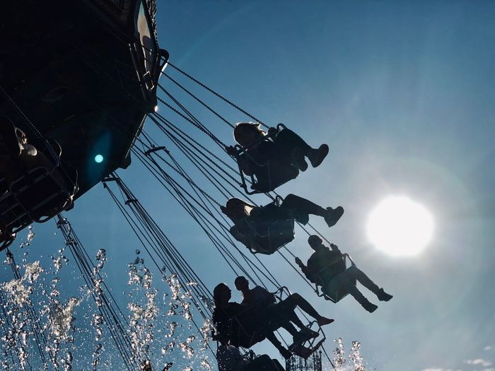 Low angle view of people enjoying chain swing ride at amusement park against sky
