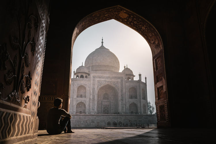 Man Looking At Taj Mahal Through Arch