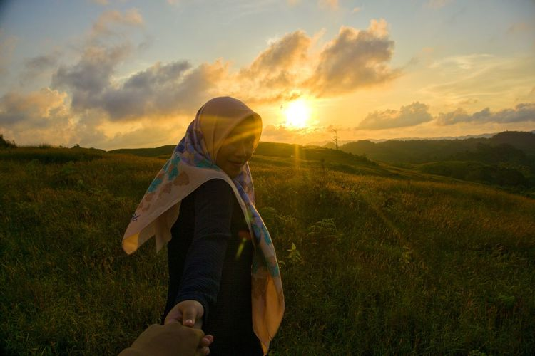 Close-up of man holding hand of girlfriend on field against sky during sunset