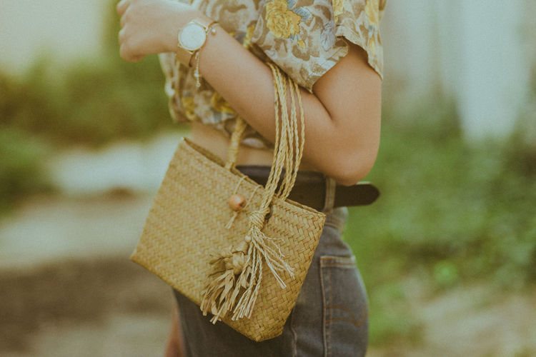 Midsection Of Woman Holding Wicker Bag While Standing Outdoors