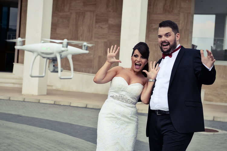 Shocked Bride And Groom Looking At Drone Against Building