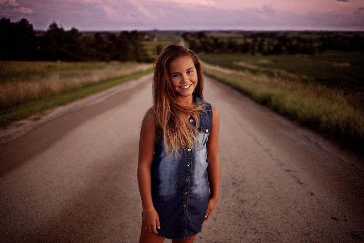 Portrait of girl standing on road at sunset