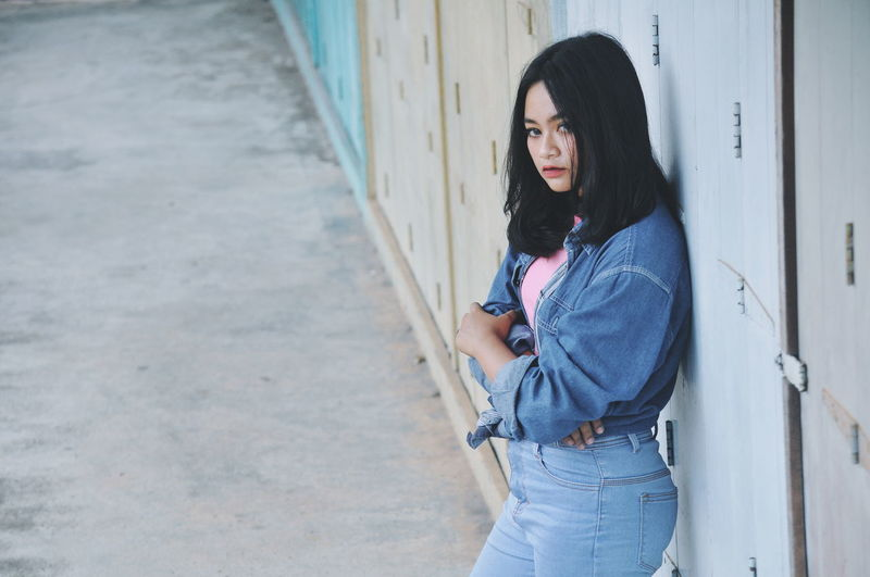 Thoughtful Woman Wearing Denim Jacket While Looking Away Against Wall