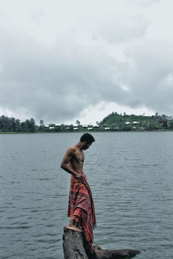 Side View Of Shirtless Mature Man With Towel Standing On Rock In Lake Against Cloudy Sky