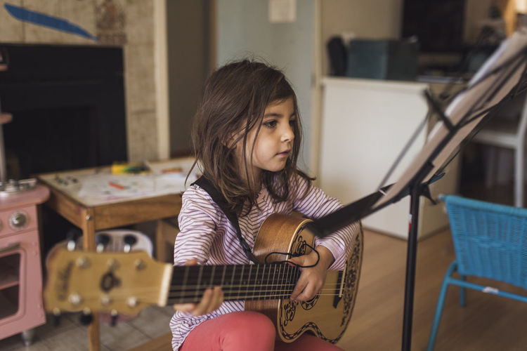 Girl playing guitar at home