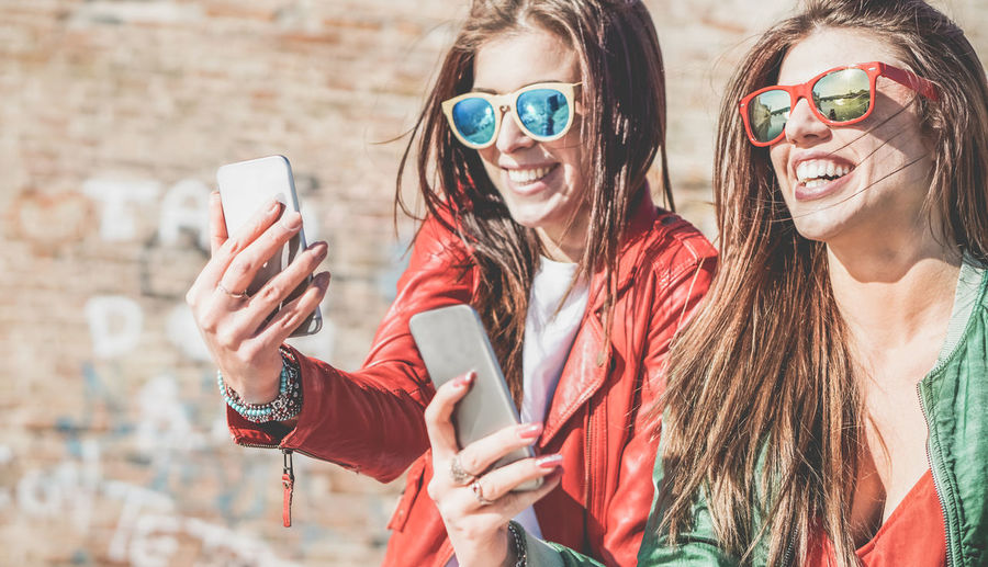Happy girls using mobile smart phones Cellphone Friends Fun Happy Moment Young Youth Adult Camera Cell Communication Day Friendship Girls Happiness Mobile Phone Selfie Smart Phone Smiling Sunglasses Technology Women
