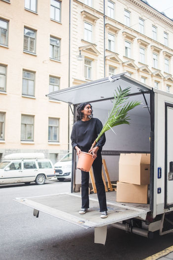 Full length of man standing in car against building