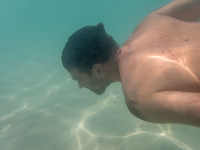 Shirtless man swimming in sea