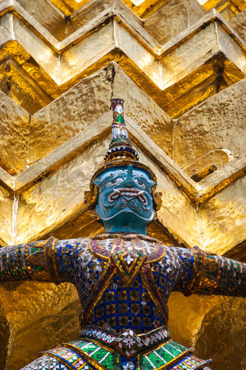 detail of a statue of a demon holding up the Golden chedi at the Wat Phra Kaew Palace, also known as the Emerald Buddha Temple. Bangkok, Thailand. Architecture Bangkok Thai Thailand Wat Phra Kaew Architecture Art And Craft Belief Buddhism Built Structure Demon Gold Colored Human Representation Landmark Low Angle View No People Place Of Worship Religion Royal Palace Sculpture Spirituality Statue Travel Destinations