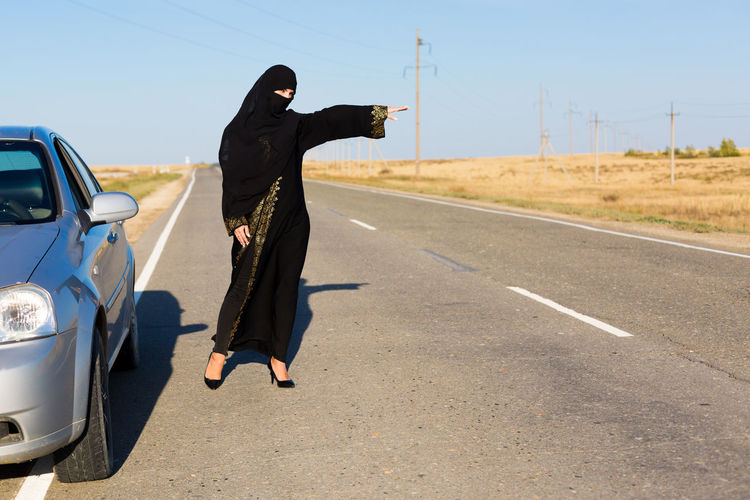 Full length of woman wearing burka standing on road against sky