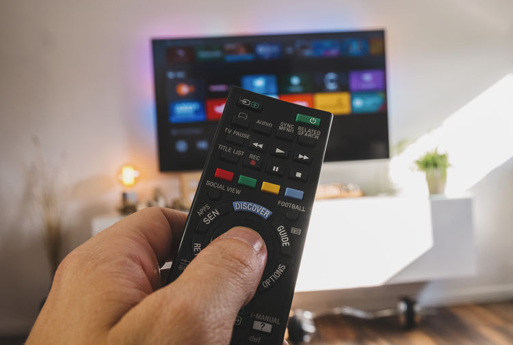 Man hand holding TV remote control zap to the smarthome menu 4k tv Blu Ray Couch DVD Homemade MOVIE POV Remote Control Close-up Communication Entertainment First Person View Focus On Foreground Holding Human Body Part Human Hand Lounge Men One Person Series Sideboard Smarthome Technology Television Watching Zap