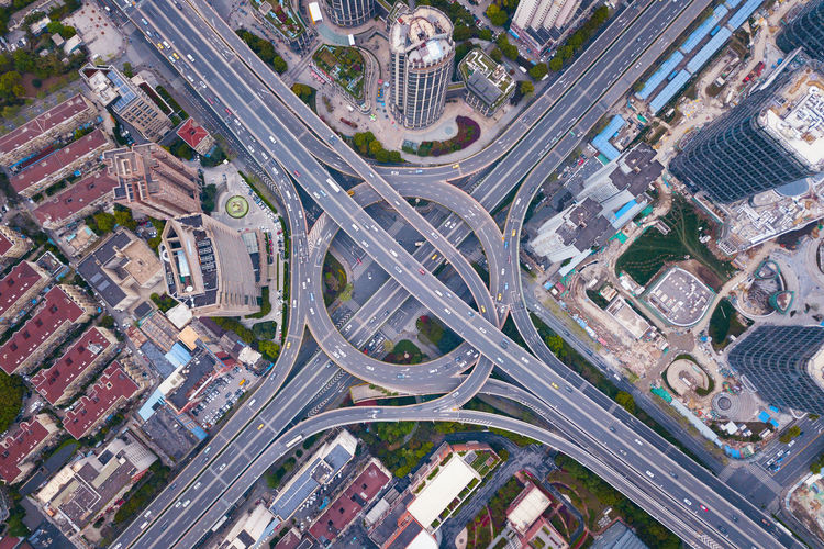 Aerial view of highway junctions with roundabout. Bridge roads shape circle in structure of architecture and transportation concept. Top view. Urban city, Shanghai, China. Shanghai China City Cityscape Buildings Architecture Downtown District Financial Road Street Aerial View Transportation High Angle View Building Exterior Built Structure Mode Of Transportation Elevated Road Highway Day No People Travel Destinations Crossroad City Life Motor Vehicle City Street Overpass Outdoors Modern Multiple Lane Highway