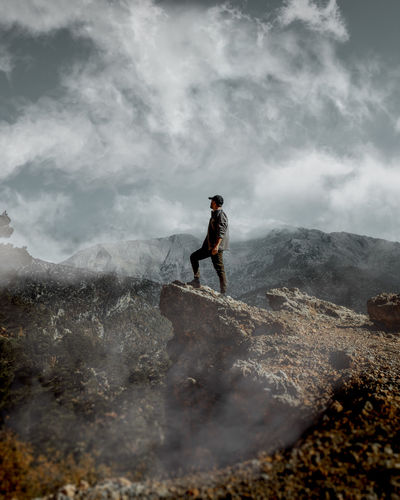 A person standing on the edge of a cliff with sky, clouds and mountains in the background.