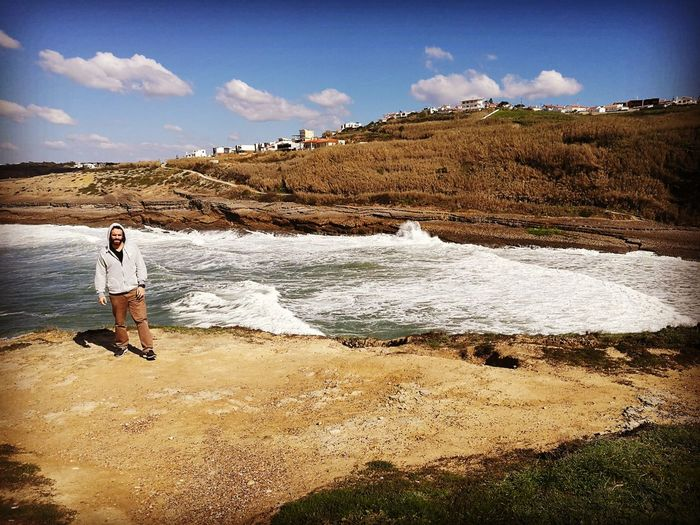 Man wearing hooded sweatshirt at praia dos coxos against sky