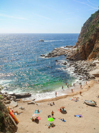 High angle view of people enjoying at beach by rocky mountain against sky at tossa de mar