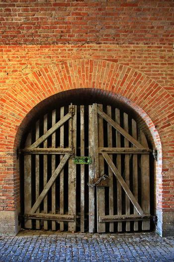 Closed door of brick wall of building