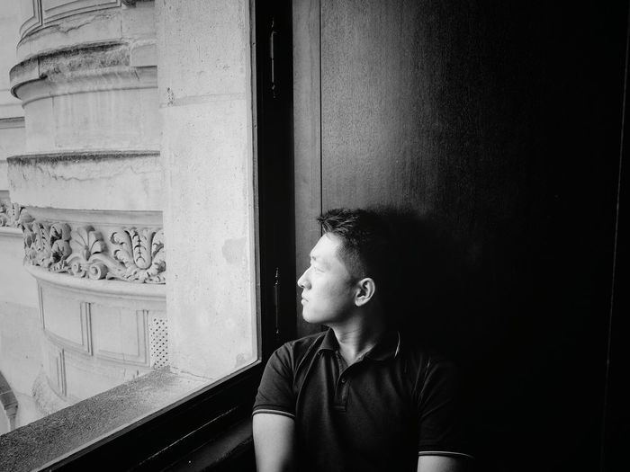 Thoughtful man looking through window