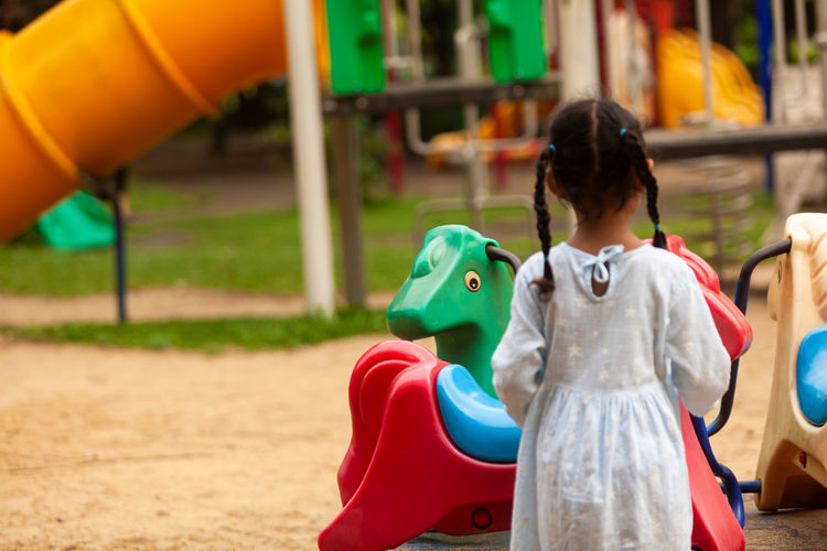 Rear view of cute girl playing at playground