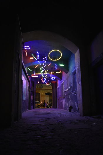 Illuminated entrance of abandoned building at night