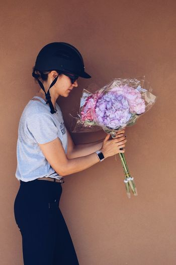 Side view of jockey holding fresh hydrangeas bouquets against wall