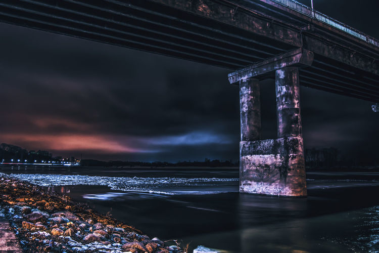 Low angle view of bridge over frozen river at night