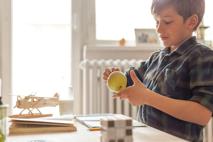 Cute elementary student playing with an apple while studying at home.