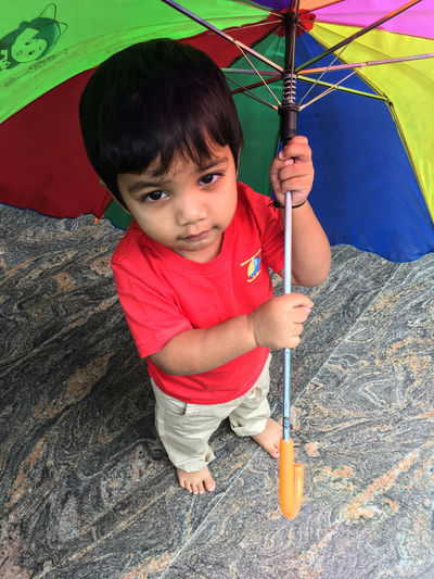 Portrait Of Cute Boy Holding Umbrella While Standing Outdoors