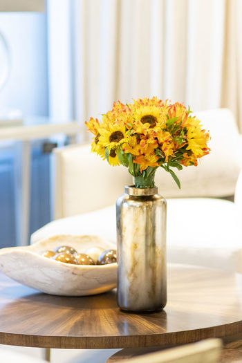 Close-up of yellow flower vase on table