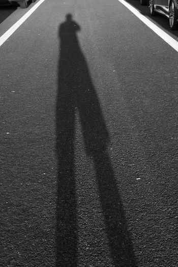 Casting a Long Shadow Black & White Black & White Photography Casting Shadows Asphalt Black And White Black And White Photography Casting A Shadow Day Focus On Shadow High Angle View Lifestyles Long Shadow - Shadow Men One Person Outdoors Real People Road Shadow Sign Street Sunlight Sunset Symbol Transportation Unrecognizable Person