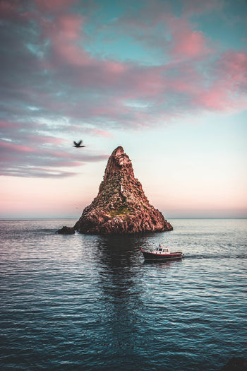 Bird, boat and stack Water Sky Sea Waterfront Cloud - Sky Beauty In Nature Scenics - Nature Rock Rock - Object Horizon Over Water Sunset Tranquil Scene Tranquility Solid Horizon Nature No People Idyllic Rock Formation Outdoors Stack Rock Acitrezza  Stack Cormorant  Catania