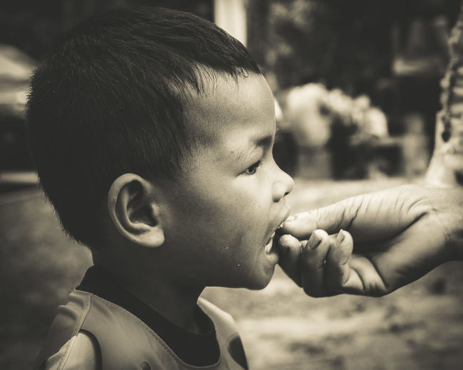 Cropped Image Of Hand Feeding Boy At Yard