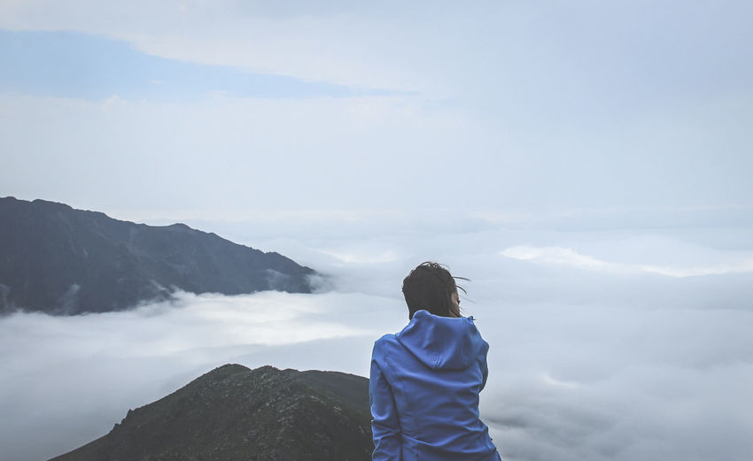 Rear view of woman looking at cloudscape while sitting on mountain